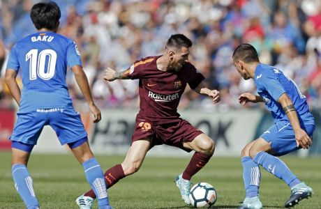 Barcelona's Lionel Messi, centre, vies for the ball with Getafe's Gaku Shibasaki, left, and Mauro Arambarri during a Spanish La Liga soccer match between Getafe and Barcelona at the Alfonso Perez stadium in Getafe, outside Madrid, Saturday, Sept. 16, 2017. Barcelona won 2-1. (AP Photo/Francisco Seco)