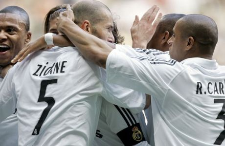 Real Madrid player Zinedine Zidane, center, from France celebrates the goal of his teammate Julio Baptista, left, from Brazil with his Brazilian teammate Roberto Carlos, right, during his Spanish League soccer match against Villarreal at the Bernabeu stadium in Madrid, Sunday, May 7, 2006. Zidane is playing his last home match for his team. (AP Photo/Jasper Juinen)