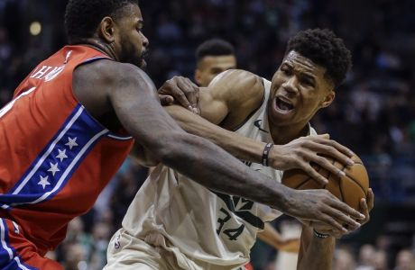 Milwaukee Bucks' Giannis Antetokounmpo, right, is tied up by Philadelphia 76ers' Amir Johnson during the second half of an NBA basketball game Monday, Jan. 29, 2018, in Milwaukee. (AP Photo/Tom Lynn)