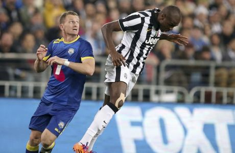 Juventus' Angelo Ogbonna, right, heads the ball away from Australian A-League's Besart Berisha during their exhibition soccer match in Sydney, Sunday, Aug. 10, 2014. (AP Photo/Rick Rycroft)