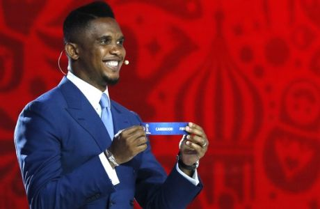 Cameroons striker Samuel Eto'o smiles as he holds the lot of Cameroon during the preliminary draw for the 2018 soccer World Cup in Konstantin Palace in St. Petersburg, Russia, Saturday, July 25, 2015. (AP Photo/Dmitry Lovetsky