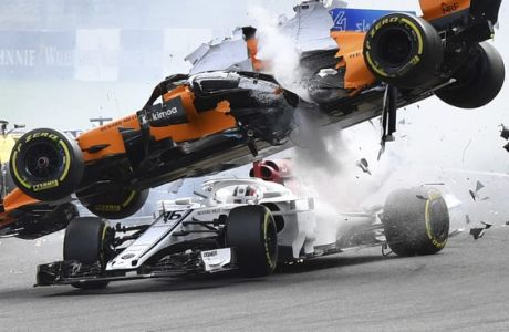 Mclaren driver Fernando Alonso of Spain, top, goes over the top of Sauber driver Charles Leclerc of Monaco as they are involved in a crash at the start of the Belgian Formula One Grand Prix in Spa-Francorchamps, Belgium, Sunday, Aug. 26, 2018. (AP Photo/Geert Vanden Wijngaert)