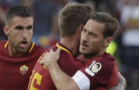 Roma's Daniele De Rossi embraces teammate Francesco Totti, right, after scoring a goal during an Italian Serie A soccer match between Roma and Genoa at the Olympic stadium in Rome, Sunday, May 28, 2017. Francesco Totti is playing his final match with Roma against Genoa after a 25-season career with his hometown club. (AP Photo/Alessandra Tarantino)