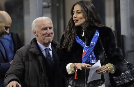 Italian coach legend Giovanni Trapattoni walks with Spanish actress Laura Barriales on the tribune prior an international friendly soccer match between Italy and Germany, at the San Siro stadium in Milan, Italy, Tuesday, Nov. 15, 2016. (AP Photo/Luca Bruno)