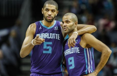 Charlotte Hornets forward Nicolas Batum, left, talks with teammate Tony Parker, both of France, during a break in the action against the Milwaukee Bucks in the second half of an NBA basketball game in Charlotte, N.C., Monday, Nov. 26, 2018. Charlotte won 110-107. (AP Photo/Nell Redmond)