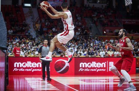 Παίκτης της Τυνησίας σε διεκδίκησης χαμένης μπάλας ενώ ο Ιρανός αντίπαλος του, παρακολουθεί. Στιγμιότυπο από τον αγώνα Τυνησία - Ιραν για το Παγκόσμιο Κύπελλο Κίνας