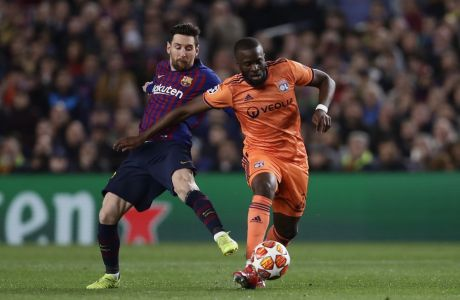 Barcelona forward Lionel Messi, left, fights for the ball with Lyon midfielder Tanguy Ndombele during the Champions League round of 16, 2nd leg, soccer match between FC Barcelona and Olympique Lyon at the Camp Nou stadium in Barcelona, Spain, Wednesday, March 13, 2019. (AP Photo/Manu Fernandez)