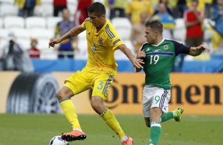 Ukraine's Yevhen Khacheridi, left, and Northern Ireland's Jamie Ward go for the ball during the Euro 2016 Group C soccer match between Ukraine and Northern Ireland at the Grand Stade in Decines-Charpieu, near Lyon, France, Thursday, June 16, 2016. (AP Photo/Laurent Cipriani)