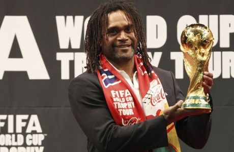 FIFA ambassador and former French player Christian Karembeu poses with the FIFA World Cup trophy during the FIFA World Cup Trophy Tour event to promote the 2014 World Cup, in Seoul, South Korea, Friday, April 4, 2014. South Korea will face Russia, Belgium and Algeria in 2014 Brazil World Cup. (AP Photo/Ahn Young-joon)