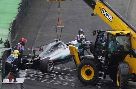 Crews remove a car from the track after Mercedes driver Lewis Hamilton, of Britain, crashed his car during the qualifying session for the Brazilian Formula One Grand Prix at the Interlagos race track in Sao Paulo, Brazil, Saturday, Nov. 11, 2017. (AP Photo/Nelson Antoine)