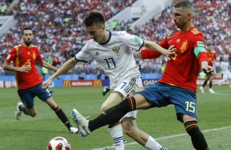 Russia's Alexander Golovin, left, challenges for the ball with Spain's Sergio Ramos during the round of 16 match between Spain and Russia at the 2018 soccer World Cup at the Luzhniki Stadium in Moscow, Russia, Sunday, July 1, 2018. (AP Photo/Victor R. Caivano)