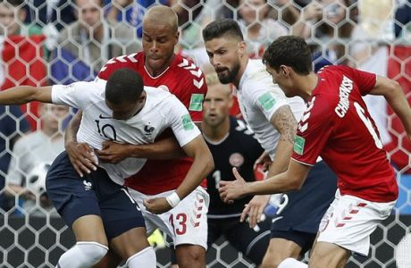 France's Kylian Mbappe, left, and Denmark's Mathias Jorgensen struggle during the group C match between Denmark and France at the 2018 soccer World Cup at the Luzhniki Stadium in Moscow, Russia, Tuesday, June 26, 2018. (AP Photo/David Vincent)