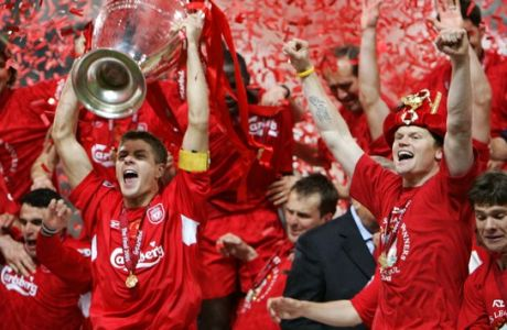 Liverpool's captain Steven Gerrard, left, holds the trophy as teammate John Arne Riise celebrates after the UEFA Champions League Final between AC Milan and Liverpool at the Ataturk Olympic Stadium in Turkey, Istanbul Wednesday May 25, 2005. Liverpool won 3-2 on penalties after the match finished 3-3 after extra time.  (AP Photo/Thomas Kienzle)