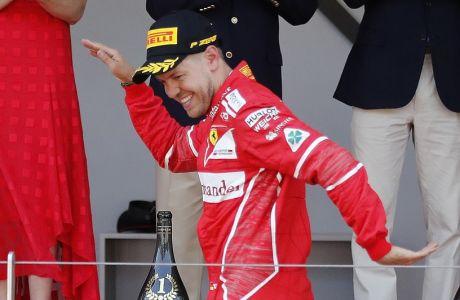 Ferrari driver Sebastian Vettel of Germany celebrates on the podium after winning the Formula One Grand Prix at the Monaco racetrack in Monaco, Sunday, May 28, 2017. (AP Photo/Frank Augstein)