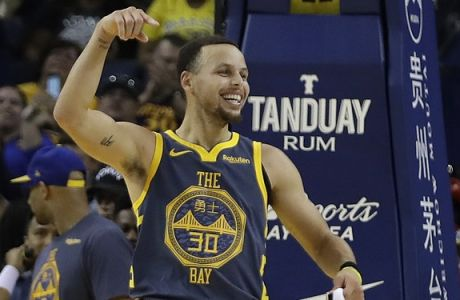 Golden State Warriors' Stephen Curry celebrates a score made Jonas Jerebko during the first half of the team's NBA basketball game against the Chicago Bulls on Friday, Jan. 11, 2019, in Oakland, Calif. (AP Photo/Ben Margot)