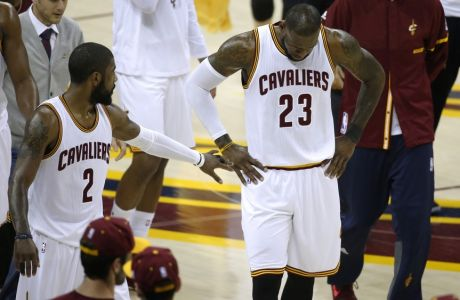 Cleveland Cavaliers guard Kyrie Irving (2) reaches out to teammate LeBron James (23), who lay on the court after contact with the Golden State Warriors during the first half of Game 3 of basketball's NBA Finals in Cleveland, Wednesday, June 7, 2017. (AP Photo/Ron Schwane)
