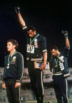 Το ημερολόγιο γράφει 16 Οκτωβρίου 1968. Απονομή για τους ολυμπιονίκες στα 200. Στο κέντρο ο Τόμι Σμιθ, πίσω του ο Τζον Κάρλος υψώνουν τις γροθιές και μαζί με τον Πίτερ Νόρμαν (μπροστά τους) γράφουν μια μοναδική ιστορία