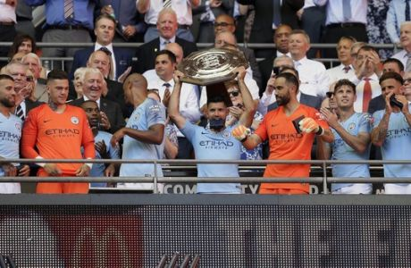 Manchester City's Sergio Aguero holds up the trophy after Manchester City won the Community Shield soccer match between Chelsea and Manchester City at Wembley, London, Sunday, Aug. 5, 2018. (AP Photo/Tim Ireland)