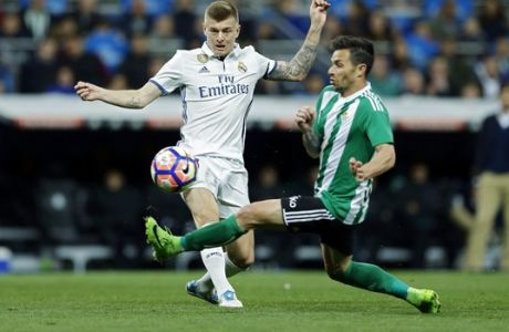 Real Madrid's Toni Kroos, left, tussles for the ball with Real Betis' Alin Tosca during a Spanish La Liga soccer match between Real Madrid and Real Betis at the Santiago Bernabeu stadium in Madrid, Sunday, March 12, 2017. (AP Photo/Francisco Seco)