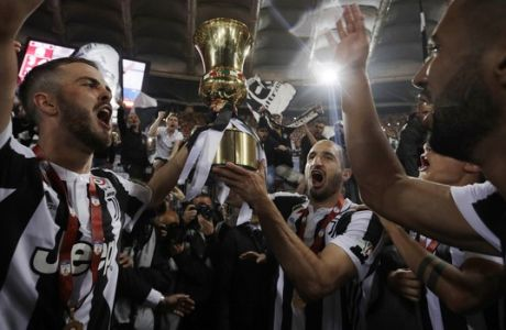 Juventus' Giorgio Chiellini, center, holds up the trophy as he celebrates with teammates Miralem Pjanic, left, Medhi Benatia, right and Paulo Dybala, second from right, after beating AC Milan 4-0 in the Italian Cup final soccer match, at the Rome Olympic stadium, Wednesday, May 9, 2018. (AP Photo/Gregorio Borgia)
