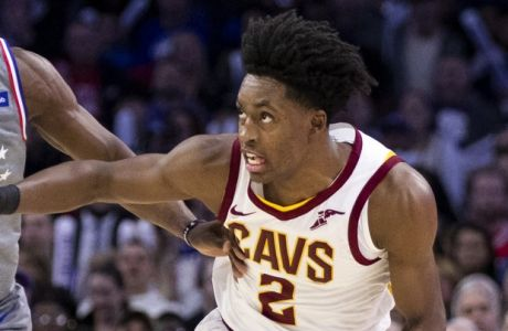 Philadelphia 76ers' Jimmy Butler, left, reaches for the loose ball while holding off Cleveland Cavaliers' Collin Sexton, right, during the second half of an NBA basketball game, Friday, Nov. 23, 2018, in Philadelphia. The Cavaliers won 121-112. (AP Photo/Chris Szagola)