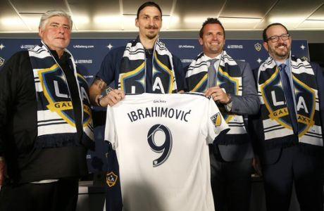 LA Galaxy's head coach Sigi Schmid, left, the Galaxy's newest player Zlatan Ibrahimovic of Sweden, team president Chris Klein and AEG president and CEO Dan Beckerman, pose with Ibrahimovic's new jersey during an MLS soccer press conference following a training session at the StubHub Center, March 30, 2018 in Carson, Calif. (AP Photo/Ringo H.W. Chiu)