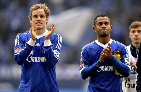 Schalke's scorers Raffael of Brazil, right, and  Teemu Pukki of Finland clap hands with fans after the German first division Bundesliga soccer match between FC Schalke 04 and TSG Hoffenheim in Gelsenkirchen, Germany, Saturday, March 30, 2013. Both substitute players scored after changed in during the second half. (AP Photo/Martin Meissner)