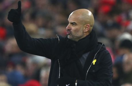 Manchester City's manager Pep Guardiola gives a thumbs up to his players during the English Premier League soccer match between Liverpool and Manchester City at Anfield Stadium, in Liverpool, England, Sunday Jan. 14, 2018. (AP Photo/Dave Thompson)