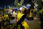 A supporter of presidential candidate Jair Bolsonaro, holds an oversized, fake rifle, as she celebrates the election runoff results in Rio de Janeiro, Brazil, Sunday, Oct. 28, 2018. Brazils Supreme Electoral Tribunal declared the far-right congressman the next president of Latin Americas biggest country. (AP Photo/Silvia Izquierdo)