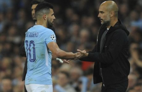 Manchester City head coach Pep Guardiola touches hands with Manchester City's Sergio Aguero as he is substituted during the Champions League Group F soccer match between Manchester City and Shakhtar Donetsk at Etihad stadium, Manchester, England, Tuesday, Sept. 26, 2017. (AP Photo/Rui Vieira)