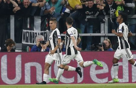 Juventus's Paulo Dybala, left, celebrates after scoring his side's first goal during a Champions League, quarterfinal, first-leg soccer match between Juventus and Barcelona, at the Juventus Stadium in Turin, Italy, Tuesday, April 11, 2017. (AP Photo/Antonio Calanni)