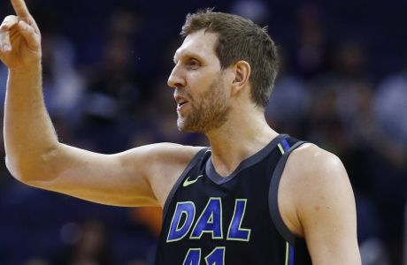 Dallas Mavericks forward Dirk Nowitzki waves to the Phoenix Suns bench prior to an NBA basketball game against the Suns, Wednesday, Jan. 31, 2018, in Phoenix. The Suns defeated the Mavericks 102-88. (AP Photo/Ross D. Franklin)