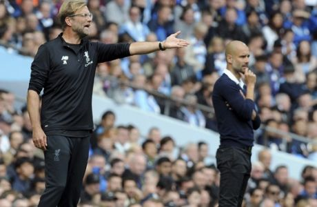 Manchester City's coach Pep Guardiola, right, and Liverpool's coach Juergen Klopp, left, attend the English Premier League soccer match between Manchester City and Liverpool at the Etihad Stadium in Manchester, England, Saturday, Sept. 9, 2017. (AP Photo/Rui Vieira)