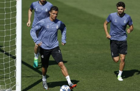 Real Madrid's Cristiano Ronaldo controls a ball as he runs followed by teammate Karim Benzema, left, and Enzo Fernandez Zidane during a training session prior at the Valdebebas stadium, in Madrid, Monday, April 17, 2017 prior to the Champions League quarterfinal second leg soccer match between FC Bayern Munich and Real Madrid. Real will face Munich on Tuesday.(AP Photo/Daniel Ochoa de Olza)