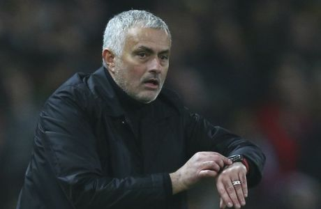 Manchester United's coach Jose Mourinho sets the extra time during the English Premier League soccer match between Manchester United and Arsenal at Old Trafford stadium in Manchester, England, Wednesday Dec. 5, 2018. (AP Photo/Dave Thompson)