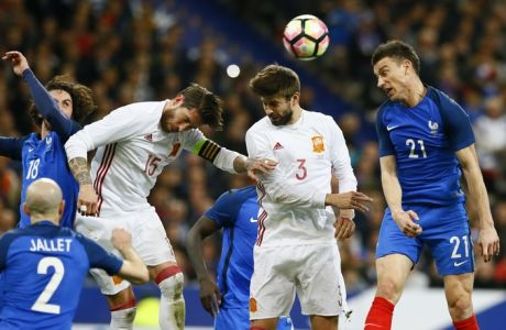 France's Adrien Rabiot, left, and teammate France's Laurent Koscielny, right, battle for the ball with Spain's Sergio Ramos, second left, and Gerard Pique during the international friendly soccer match between France and Spain at the Stade de France, Paris, Tuesday, March 28, 2017. (AP Photo/Francois Mori)