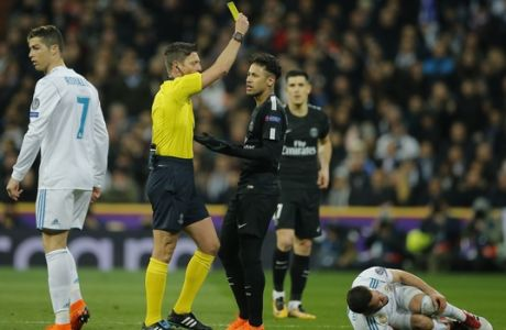 PSG's Neymar, center, receives a yellow card during the Champions League soccer match, round of 16, 1st leg between Real Madrid and Paris Saint Germain at the Santiago Bernabeu stadium in Madrid, Spain, Wednesday, Feb. 14, 2018. (AP Photo/Paul White)