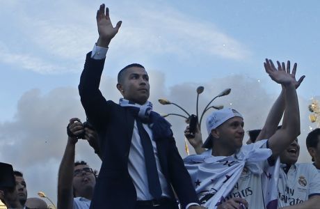 Real Madrid's Cristiano Ronaldo, left, waves on top of an open-topped bus in Cibeles square to celebrate with the team after winning the Champions League final, Madrid, Spain, Sunday June 4, 2017. Real Madrid became the first team in the Champions League era to win back-to-back titles with their 4-1 victory over Juventus in Cardiff Saturday. (AP Photo/Paul White)