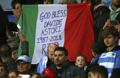 Italian supporters hold up their national flag in honor of recently deceased player Davide Astori before the international friendly soccer match between Argentina and Italy at the Etihad Stadium in Manchester, England, Friday, March 23, 2018. (AP Photo/Dave Thompson)