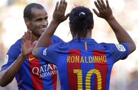 Former FC Barcelona player Ronaldinho, right, gestures to his teammate Rivaldo during the friendly soccer match between FC Barcelona legends and Manchester United legends at the Camp Nou stadium in Barcelona, Spain, Friday, June, 30, 2017. (AP Photo/Manu Fernandez)