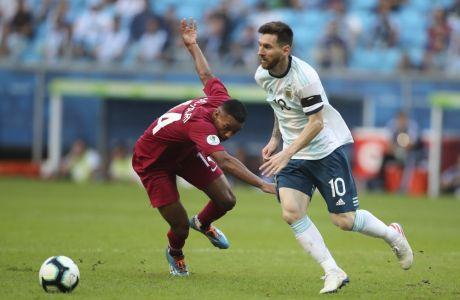 Argentina's Lionel Messi, right, dribbles past Qatar's Salem Al Hajri during a Copa America Group B soccer match at the Arena do Gremio in Porto Alegre, Brazil, Sunday, June 23, 2019. (AP Photo/Edison Vara)