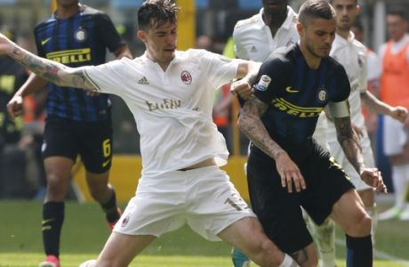 AC Milan's Alessio Romagnoli, left, and Inter Milan's Mauro Icardi vie for the ball during an Italian Serie A soccer match between Inter Milan and AC Milan, at the San Siro stadium in Milan, Italy, Saturday, April15, 2017. (AP Photo/Antonio Calanni)
