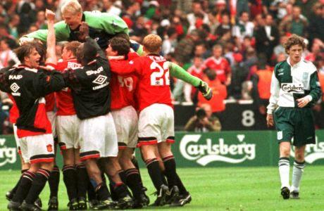Ο Στιβ ΜακΜάναμαν απογοητευμένος δίπλα από τους παίκτες της Μάντσεστερ Γιουνάιτεντ που πανηγυρίζουν την επικράτηση τους επί της Λίβερπουλ στον τελικό του FA Cup στο 'Wembley', στις 11 Μαΐου του 1996. (AP PHOTO/ Max Nash)
