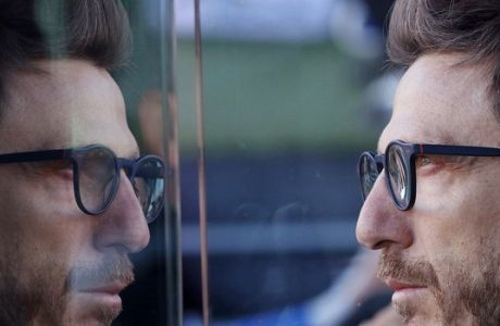 Sassuolo coach Eusebio Di Francesco's face is reflected on a bench glass during the Serie A soccer match between Udinese and Sassuolo at the Friuli Stadium in Udine, Italy, Sunday, Nov. 1, 2015. (AP Photo/Paolo Giovannini)