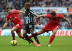 Newcastle United's Rolando Aarons, center, vies for the ball with Liverpool's Joe Allen, left, and captain Steven Gerrard, right, during their English Premier League soccer match at St James' Park, Newcastle, England, Saturday, Nov. 1, 2014. (AP Photo/Scott Heppell)