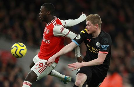 Arsenal's Nicolas Pepe, left, fights for the ball with Manchester City's Kevin De Bruyne during the English Premier League soccer match between Arsenal and Manchester City, at the Emirates Stadium in London, Sunday, Dec. 15, 2019. (AP Photo/Ian Walton)