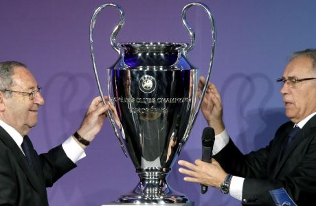 Former players of Real Madrid, Francisco Gento, left, and Amancio Amaro Varela, right, deliver the trophy during a hand over reception of the Champions League trophy in Berlin, Germany, Monday, April 27, 2015. The city of Berlin is host of the Champions League Final 2015. (AP Photo/Michael Sohn)