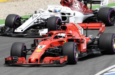 Ferrari driver Sebastian Vettel of Germany, front, and Sauber driver Marcus Ericsson of Sweden steer their cars during the qualifying session at the Hockenheimring racetrack in Hockenheim, Germany, Saturday, July 21, 2018. The German Formula One Grand Prix will be held on Sunday, July 22, 2018. (AP Photo/Jens Meyer)