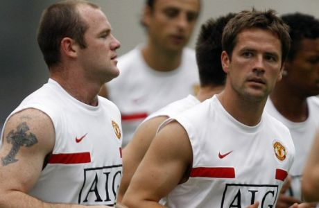Manchester United's Michael Owen, right, and Wayne Rooney, left, run with their teammates during a soccer training session in Hangzhou, China, Saturday, July 25, 2009. (AP Photo/Eugene Hoshiko)
