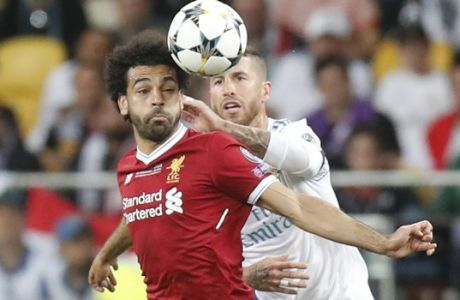 Real Madrid's Sergio Ramos, right, and Liverpool's Mohamed Salah challenge for the ball during the Champions League Final soccer match between Real Madrid and Liverpool at the Olimpiyskiy Stadium in Kiev, Ukraine, Saturday, May 26, 2018. (AP Photo/Efrem Lukatsky)